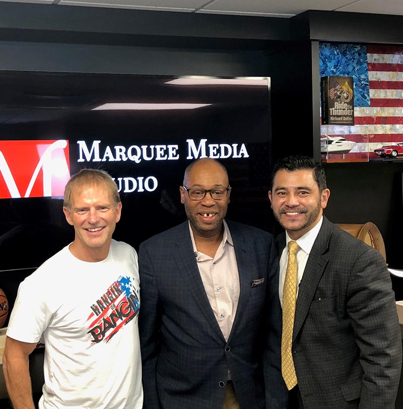 Image of 3 men, 2 are staff of 247Med and the other is the radio host.The radio studio called Marquee Media