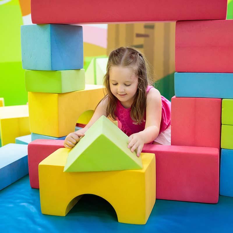 Little girl plating in a foam block castle