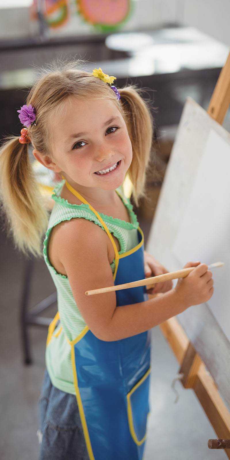 Image contains a little girl with pony tails painting on a canvas while smiling at the camera.