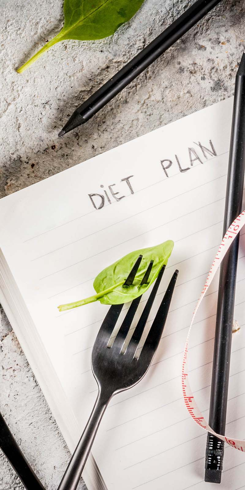Image of a journal with the words Diet Plan on the page. The book is laying on a cement along with a pen, measure tape and a fork that is piercing a leaf of lettuce