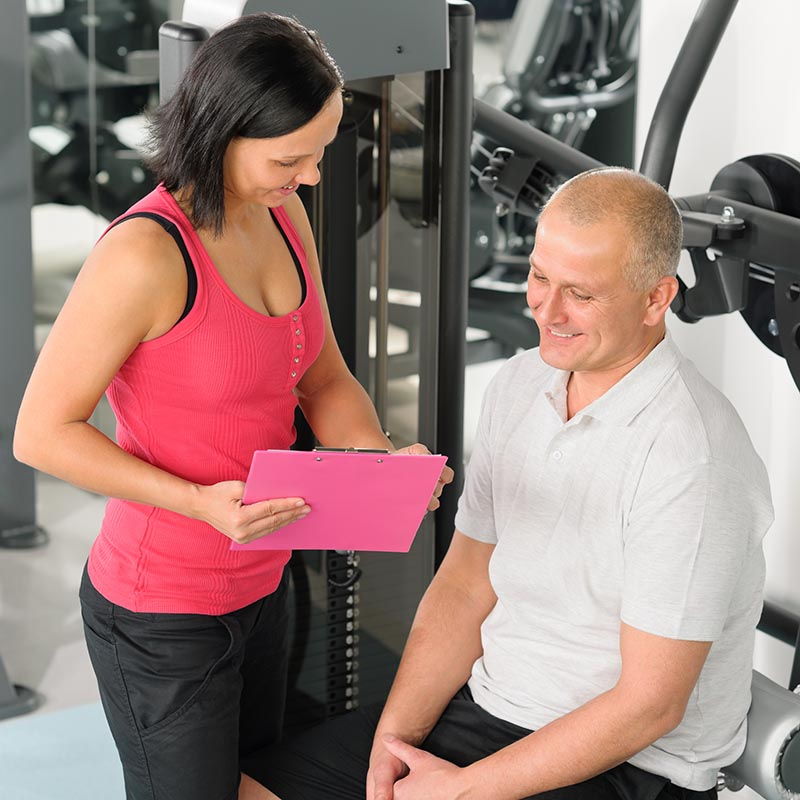 Image of a woman holding a pink folder while coaching a middle aged man to do leg curls on a machine.